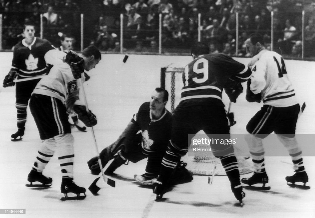 Goalie <a gi-track='captionPersonalityLinkClicked' href=/galleries/search?phrase=Johnny+Bower&family=editorial&specificpeople=239053 ng-click='$event.stopPropagation()'>Johnny Bower</a> #1 of the Toronto Maple Leafs looks to make the save as Ralph Backstrom #6 of the Montreal Canadiens flips the puck into the air as Kent Douglas #19 of the Maple Leafs and Claude Provost #14 of the Canadiens fight for position on October 28, 1964 at the Maple Leaf Gardens in Toronto, Ontario, Canada.