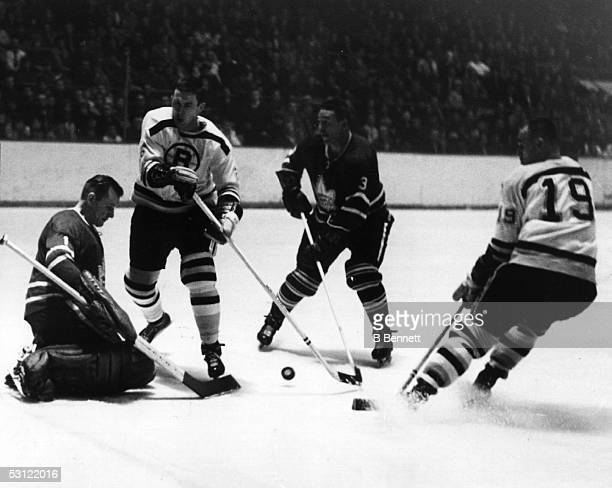 Goalie Johnny Bower of the Toronto Maple Leafs looks to make the save as his teammate Marcel Pronovost looks to defend against Don Awrey and Reggie...