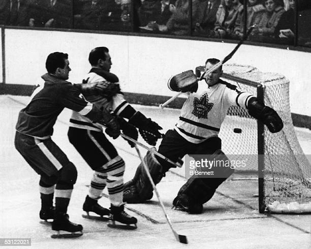 Goalie Johnny Bower of the Toronto Maple Leafs looks to make the save as teammate Bob Baun defends against Norm Ullman of the Detroit Red Wings on...