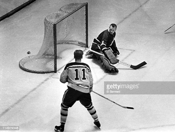 Goalie Johnny Bower of the Toronto Maple Leafs made the save against Tommy Williams of the Boston Bruins as the puck ended up behind the net during...