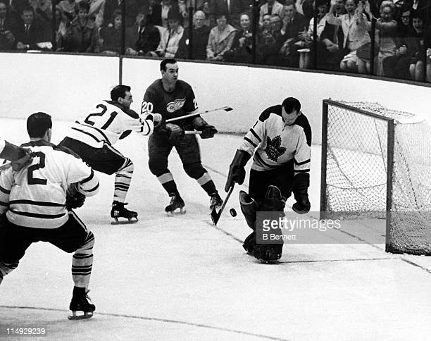Goalie Johnny Bower of the Toronto Maple Leafs makes the save as his teammates Bobby Baun and Carl Brewer box out Paker MacDonald of the Detroit Red...