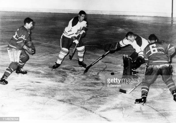 Goalie Johnny Bower of the Toronto Maple Leafs makes the save as his teammate Tim Horton tries to help with the rebound as Bob Rousseau and Ralph...