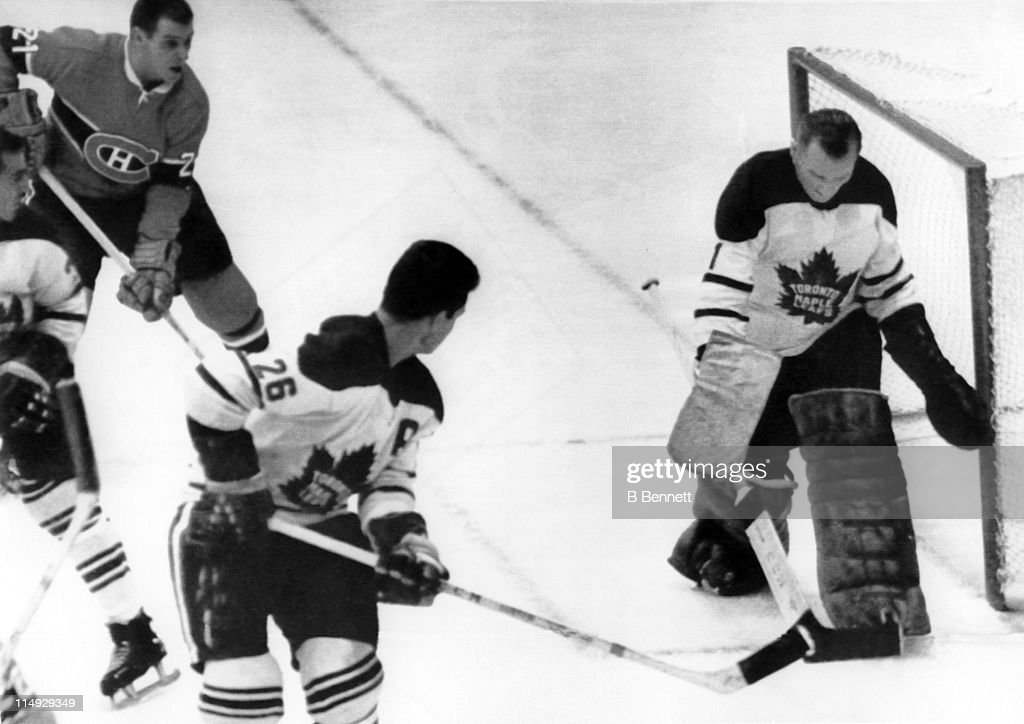 Goalie <a gi-track='captionPersonalityLinkClicked' href=/galleries/search?phrase=Johnny+Bower&family=editorial&specificpeople=239053 ng-click='$event.stopPropagation()'>Johnny Bower</a> #1 of the Toronto Maple Leafs makes the save as his teammate Allan Stanley #26 and Gilles Tremblay #21 of the Montreal Canadiens look for the rebound on October 16, 1963 at the Montreal Forum in Montreal, Quebec, Canada.