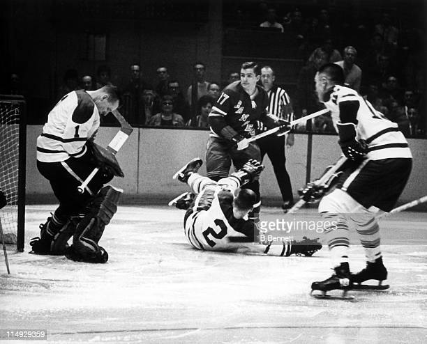Goalie Johnny Bower of the Toronto Maple Leafs makes the save as his teammates Dave Keon and Larry Hillman look to block out Walt Tkaczuk of the New...
