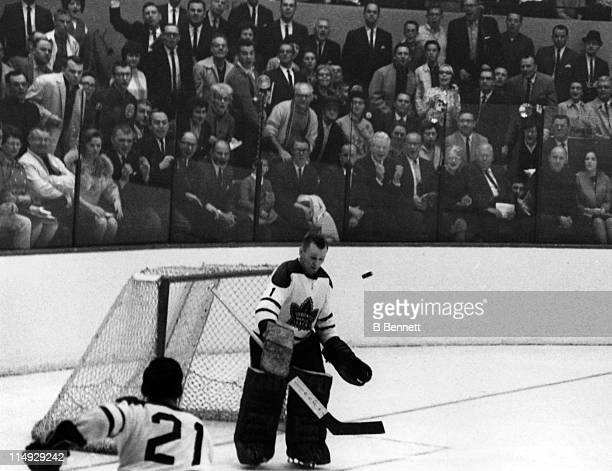 Goalie Johnny Bower of the Toronto Maple Leafs makes the save as the crowd looks on during Game 3 of the 1964 Stanley Cup Finals against the Detroit...