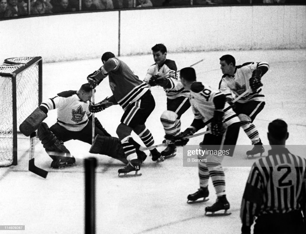 Goalie <a gi-track='captionPersonalityLinkClicked' href=/galleries/search?phrase=Johnny+Bower&family=editorial&specificpeople=239053 ng-click='$event.stopPropagation()'>Johnny Bower</a> #1 of the Toronto Maple Leafs makes the save on Ken Hodge #14 of the Chicago Blackhawks as George Armstrong #10, Tim Horton #7 and Allan Stanley #26 of the Maple Leafs try to clear the rebound on January 29, 1967 at the Chicago Stadium in Chicago, Illinois.