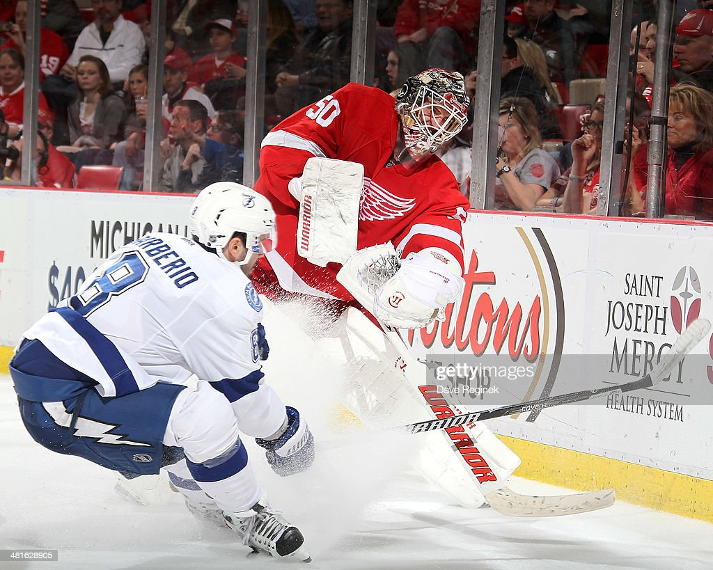 Goalie <a gi-track='captionPersonalityLinkClicked' href=/galleries/search?phrase=Jonas+Gustavsson&family=editorial&specificpeople=886789 ng-click='$event.stopPropagation()'>Jonas Gustavsson</a> #50 of the Detroit Red Wings plays the puck behind the net as <a gi-track='captionPersonalityLinkClicked' href=/galleries/search?phrase=Mark+Barberio&family=editorial&specificpeople=4819242 ng-click='$event.stopPropagation()'>Mark Barberio</a> #8 of the Tampa Bay Lightning pressures him during an NHL game on March 30, 2014 at Joe Louis Arena in Detroit, Michigan. Detroit defeated Tampa Bay 3-2
