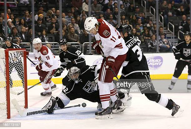 Goalie Jonathan Quick of the Los Angeles Kings dives to stop a shot by Martin Hanzal of the Phoenix Coyotes as King defenseman Willie Mitchell...