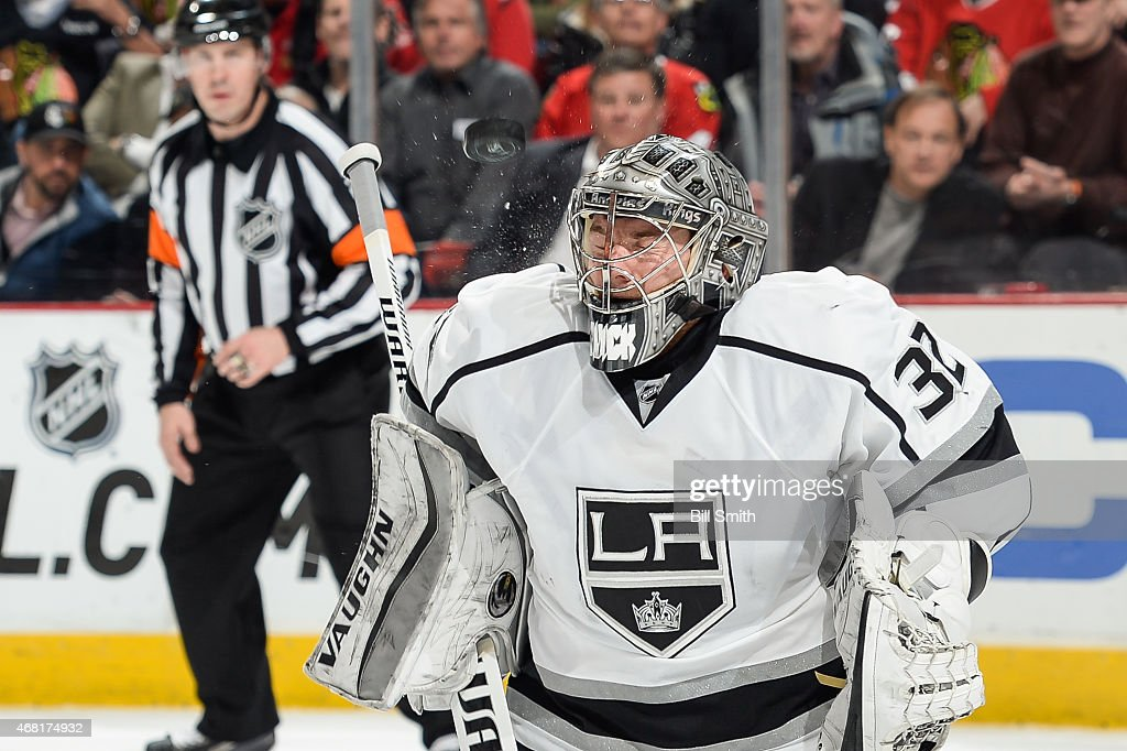 Goalie Jonathan Quick of the Los Angeles Kings is hit by the puck during the NHL game against the Chicago Blackhawks at the United Center on March 30...