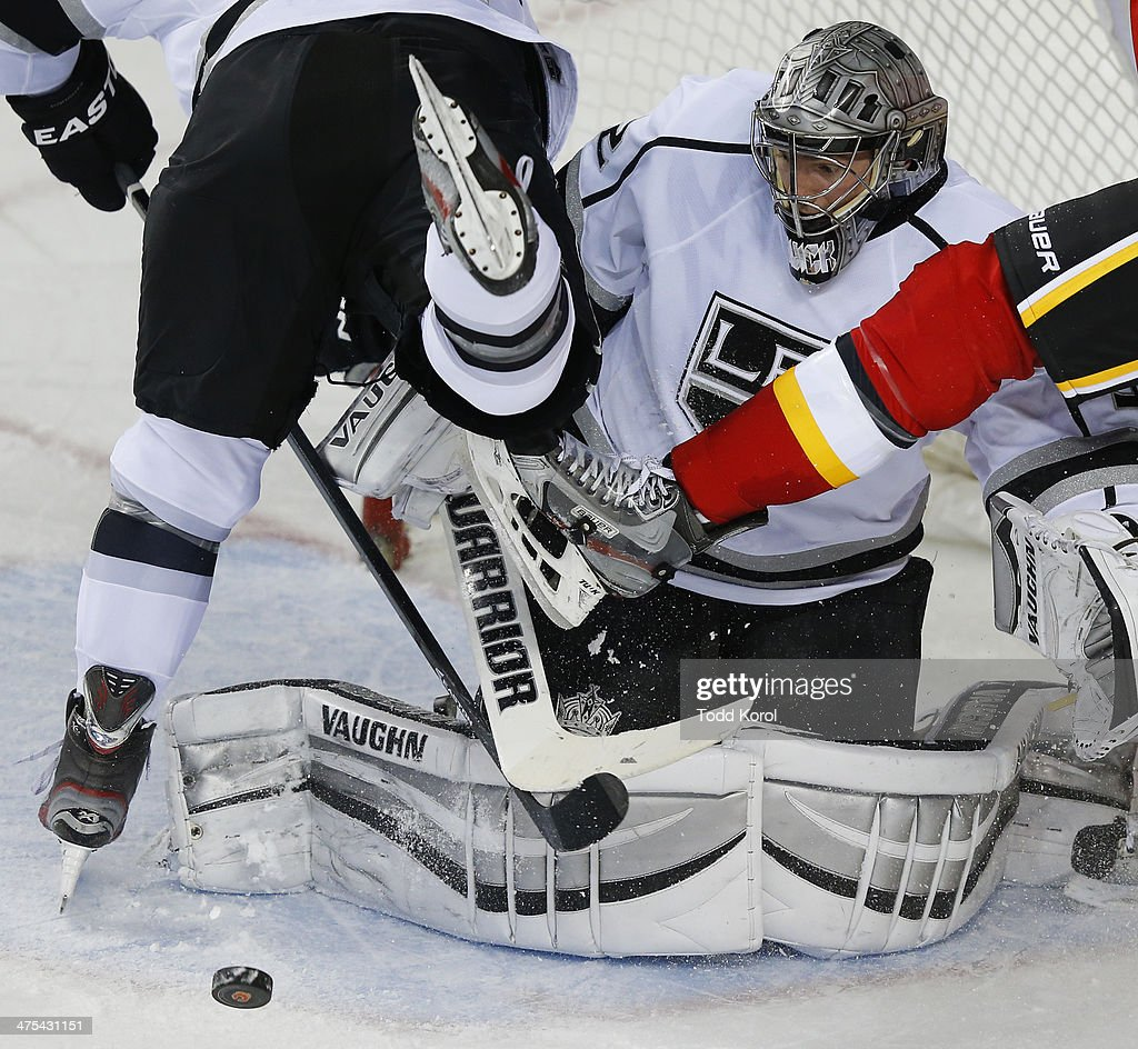 Goalie <a gi-track='captionPersonalityLinkClicked' href=/galleries/search?phrase=Jonathan+Quick&family=editorial&specificpeople=2271852 ng-click='$event.stopPropagation()'>Jonathan Quick</a> of the Los Angeles Kings keeps his eye on the puck as skates fly in front of his face during the third period of their NHL hockey game at the Scotiabank Saddledome February 27, 2014 in Calgary, Alberta, Canada.