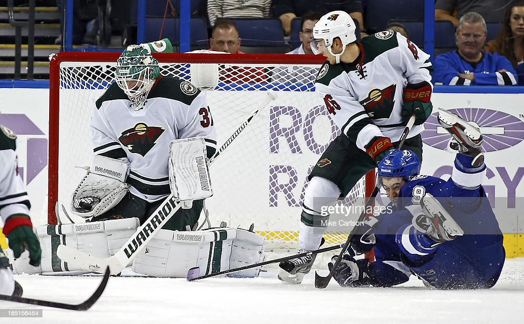 Goalie <a gi-track='captionPersonalityLinkClicked' href=/galleries/search?phrase=Josh+Harding&family=editorial&specificpeople=700587 ng-click='$event.stopPropagation()'>Josh Harding</a> #37 of the Minnesota Wild makes a save in front of <a gi-track='captionPersonalityLinkClicked' href=/galleries/search?phrase=Jared+Spurgeon&family=editorial&specificpeople=4594192 ng-click='$event.stopPropagation()'>Jared Spurgeon</a> #46 and <a gi-track='captionPersonalityLinkClicked' href=/galleries/search?phrase=Tyler+Johnson+-+Ice+Hockey+Player&family=editorial&specificpeople=14574766 ng-click='$event.stopPropagation()'>Tyler Johnson</a> #9 of the Tampa Bay Lightning at the Tampa Bay Times Forum on October 17, 2013 in Tampa, Florida.