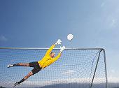 Goalie jumping to block soccer ball