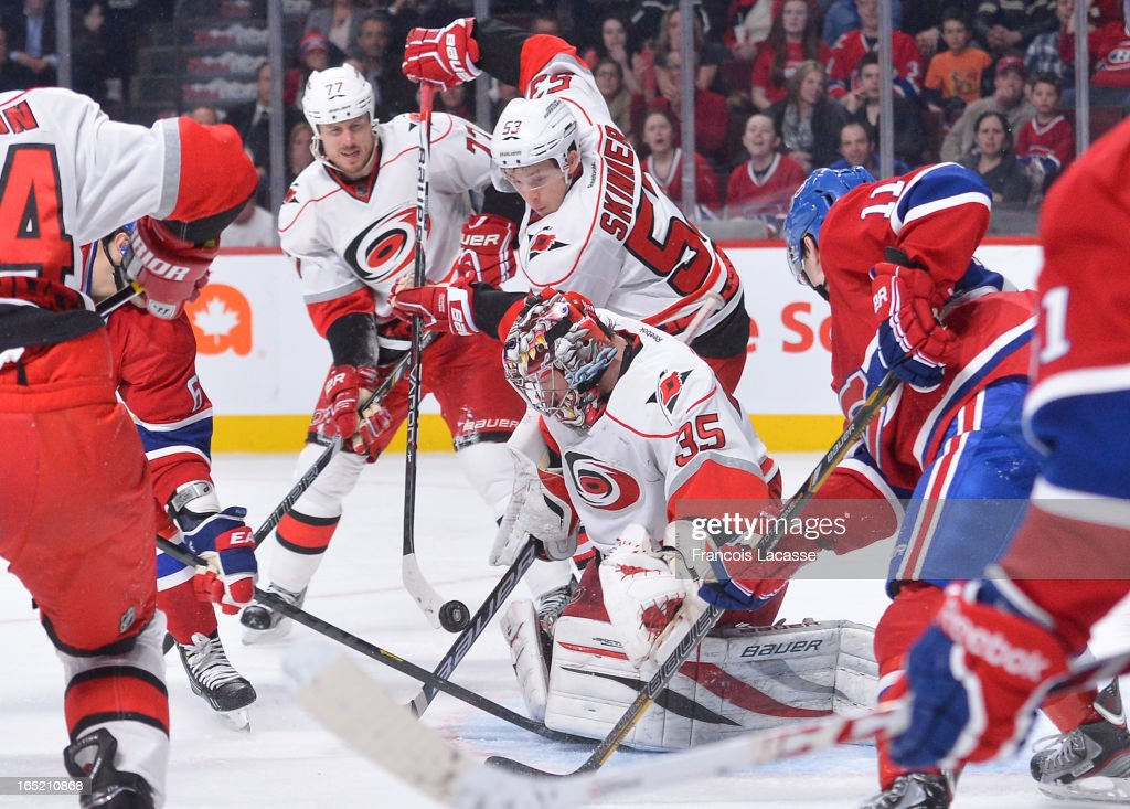 Goalie Justin Peters #35 of the Carolina Hurricanes gets help from teammate <a gi-track='captionPersonalityLinkClicked' href=/galleries/search?phrase=Jeff+Skinner&family=editorial&specificpeople=3147596 ng-click='$event.stopPropagation()'>Jeff Skinner</a> #53 as he tries to cover a loose puck during the NHL game against the Montreal Canadiens on April 1, 2013 at the Bell Centre in Montreal, Quebec, Canada.