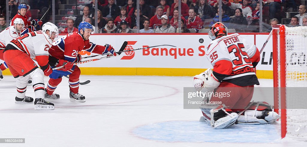 Goalie Justin Peters #35 of the Carolina Hurricanes makes a save against <a gi-track='captionPersonalityLinkClicked' href=/galleries/search?phrase=Josh+Gorges&family=editorial&specificpeople=550446 ng-click='$event.stopPropagation()'>Josh Gorges</a> #26 of the Montreal Canadiens during the NHL game on April 1, 2013 at the Bell Centre in Montreal, Quebec, Canada.