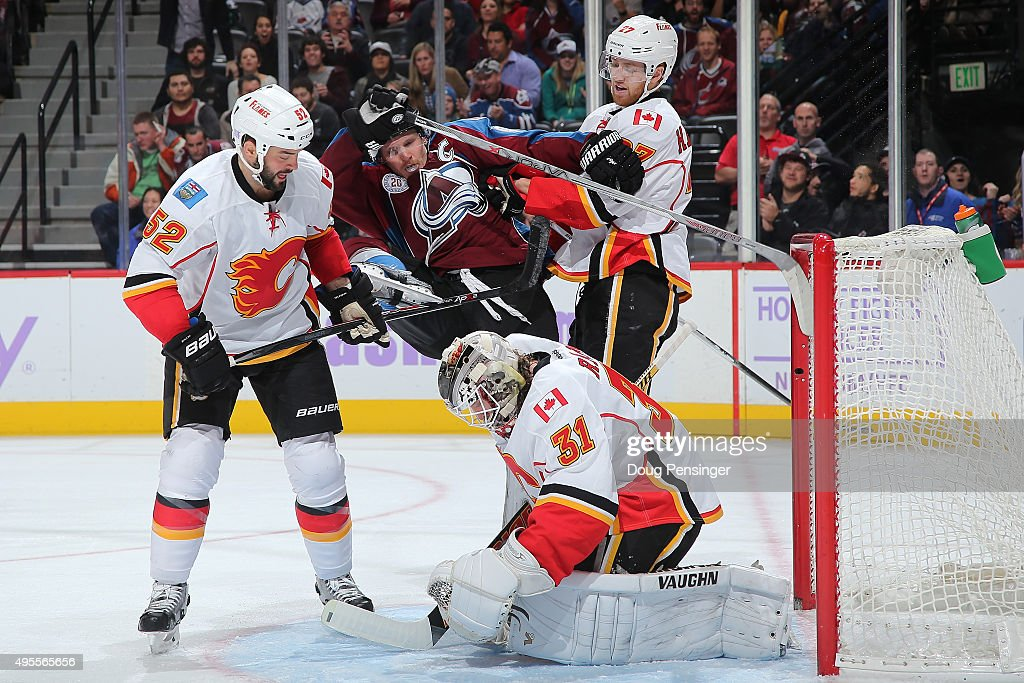 Goalie Karri Ramo #31 of the Calgary Flames makes a save as Dougie Hamilton #27 of the Calgary Flames puts a hit on Gabriel Landeskog #92 of the Colorado Avalanche and Brandon Bollig #52 of the Calgary Flames follows the action at Pepsi Center on November 3, 2015 in Denver, Colorado. The Avalanche defeated the Flames 6-3.
