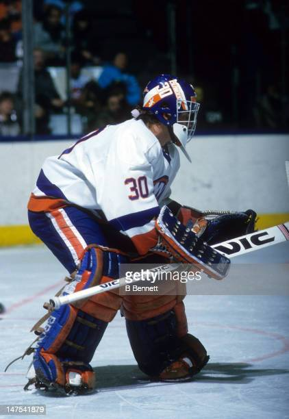 Goalie Kelly Hrudey of the New York Islanders makes the save during an NHL game in January 1988 at the Nassau Coliseum in Uniondale New York
