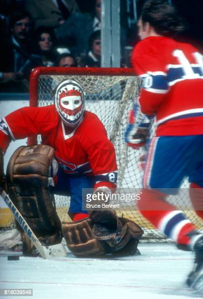 Goalie Ken Dryden of the Montreal Canadiens looks to pass the puck to his teammate Guy Lafleur during an NHL game against the New York Islanders...