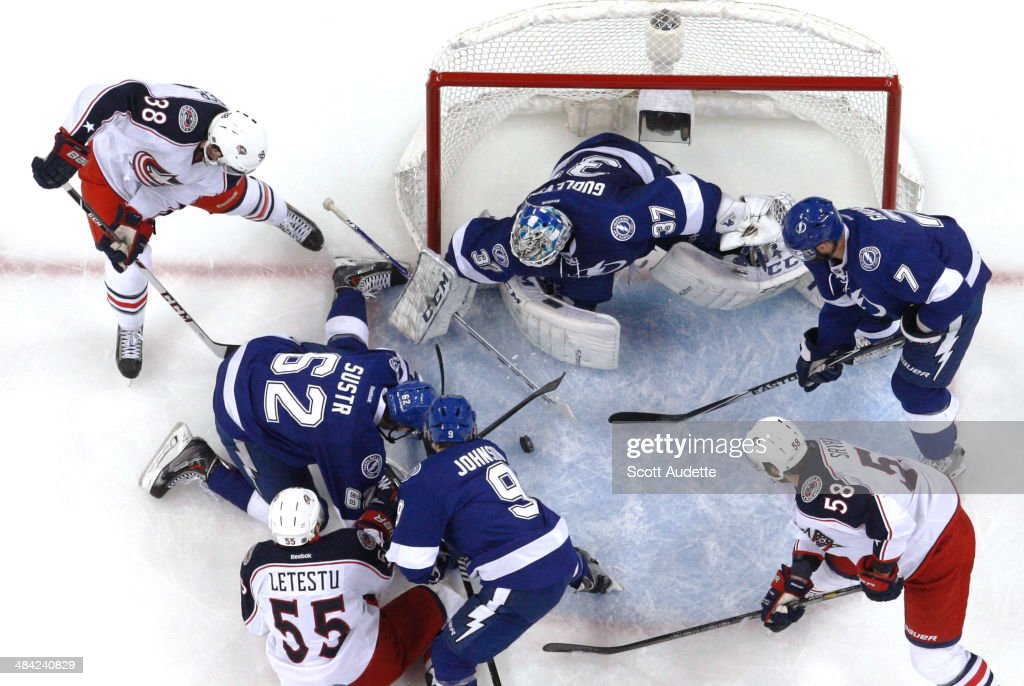 Goalie Kristers Gudlevskis #37 of the Tampa Bay Lightning looks for the puck while teammates Andrej Sustr #62, <a gi-track='captionPersonalityLinkClicked' href=/galleries/search?phrase=Tyler+Johnson+-+Giocatore+di+hockey+su+ghiaccio&family=editorial&specificpeople=14574766 ng-click='$event.stopPropagation()'>Tyler Johnson</a> #9, and <a gi-track='captionPersonalityLinkClicked' href=/galleries/search?phrase=Radko+Gudas&family=editorial&specificpeople=5648763 ng-click='$event.stopPropagation()'>Radko Gudas</a> #7 battle against <a gi-track='captionPersonalityLinkClicked' href=/galleries/search?phrase=Mark+Letestu&family=editorial&specificpeople=4601071 ng-click='$event.stopPropagation()'>Mark Letestu</a> #55, <a gi-track='captionPersonalityLinkClicked' href=/galleries/search?phrase=Boone+Jenner&family=editorial&specificpeople=6480665 ng-click='$event.stopPropagation()'>Boone Jenner</a> #38, and <a gi-track='captionPersonalityLinkClicked' href=/galleries/search?phrase=David+Savard&family=editorial&specificpeople=4630692 ng-click='$event.stopPropagation()'>David Savard</a> #58 of the Columbus Blue Jackets during the first period at the Tampa Bay Times Forum on April 11, 2014 in Tampa, Florida.