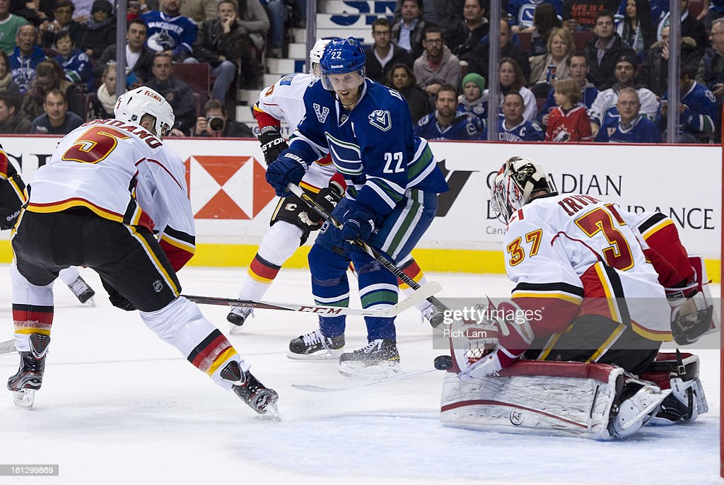 Goalie Leland Irving #37 of the Calgary Flames makes a glove save to stop <a gi-track='captionPersonalityLinkClicked' href=/galleries/search?phrase=Daniel+Sedin&family=editorial&specificpeople=202492 ng-click='$event.stopPropagation()'>Daniel Sedin</a> #22 of the Vancouver Canucks as <a gi-track='captionPersonalityLinkClicked' href=/galleries/search?phrase=Mark+Giordano&family=editorial&specificpeople=696867 ng-click='$event.stopPropagation()'>Mark Giordano</a> #5 of the Calgary Flames looks on during the second period in NHL action on February 09, 2013 at Rogers Arena in Vancouver, British Columbia, Canada.