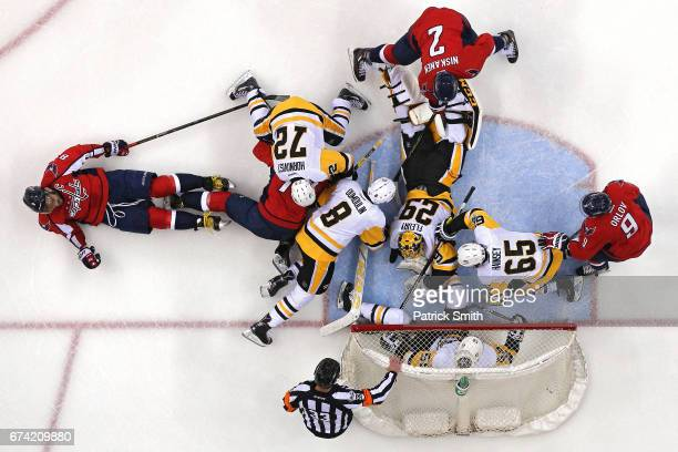 Goalie MarcAndre Fleury of the Pittsburgh Penguins makes a save as Pittsburgh Penguins and Washington Capitals players battle for the puck in the...