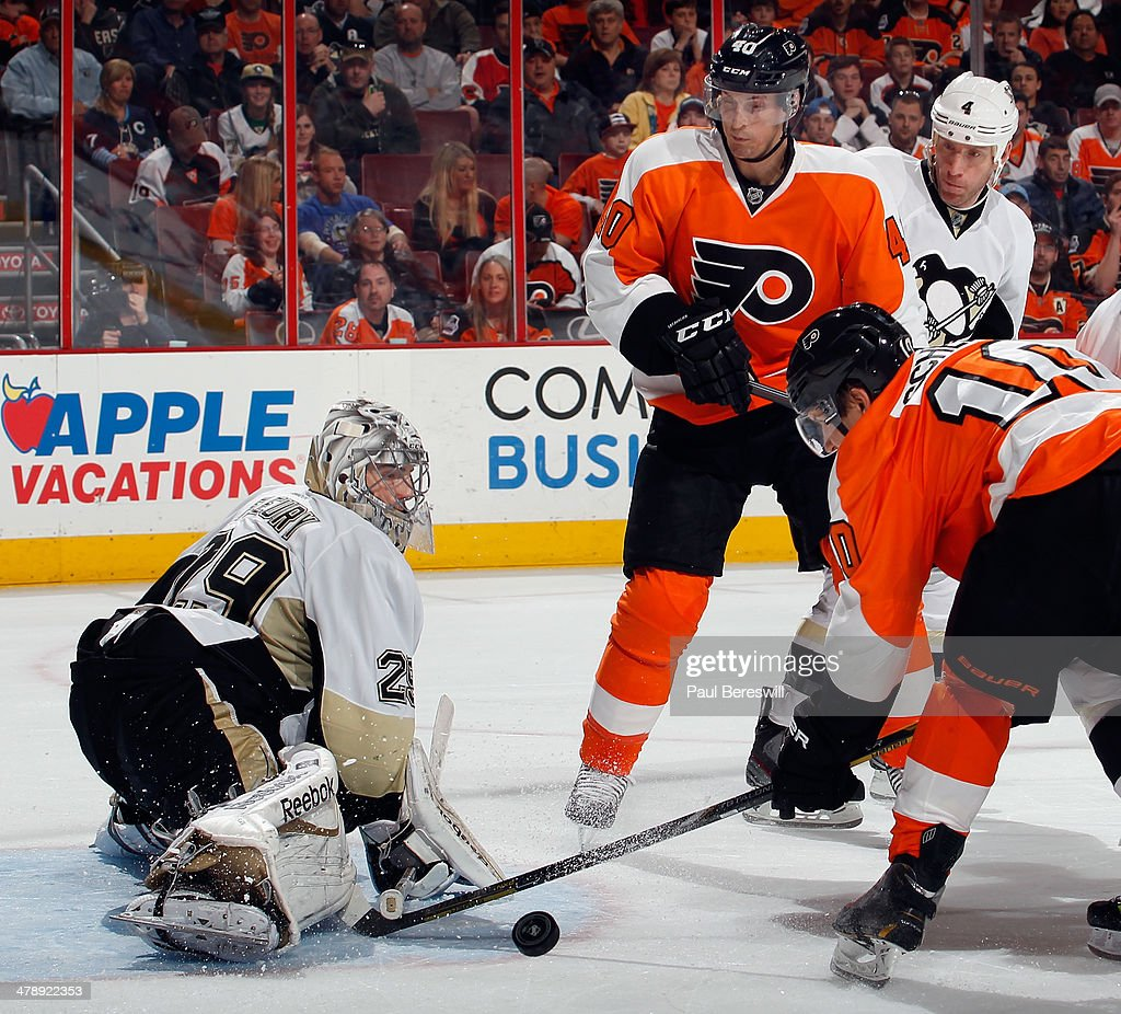 Goalie Marc-Andre Fleury #29 of the Pittsburgh Penguins makes a save on a shot by Brayden Schenn #10 of the Philadelphia Flyers as Vincent Lecavalier #40 of the Flyers watches in the second period of an NHL hockey game at Wells Fargo Center on March 15, 2014 in Philadelphia, Pennsylvania.