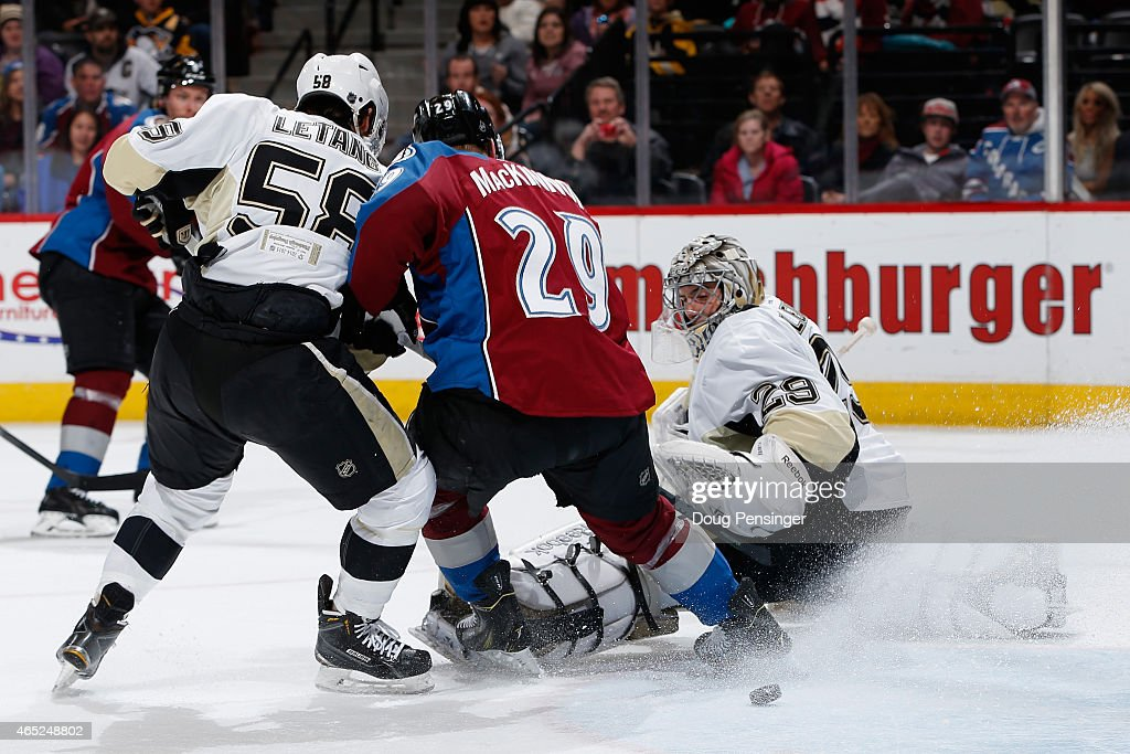 Goalie MarcAndre Fleury of the Pittsburgh Penguins watches as Nathan MacKinnon of the Colorado Avalanche deflects the puck against Kris Letang of the...