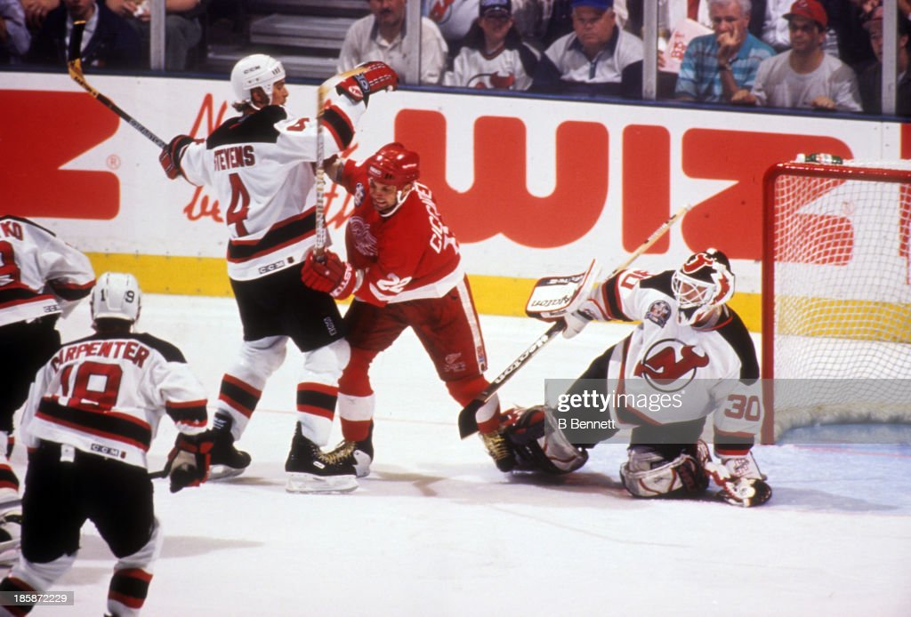 Goalie Martin Brodeur defends the net as his teammate Scott Stevens and Dino Ciccarelli of the Detroit Red Wings battle in front during Game 4 of the...
