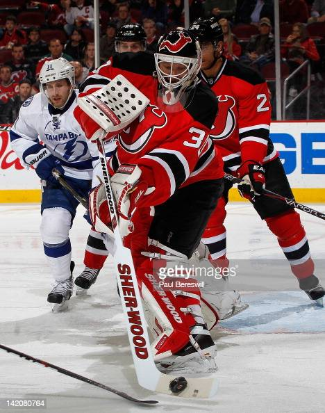 Goalie Martin Brodeur of the New Jersey Devils clears the puck away under pressure as Lightning's Tom Pyatt skates in from behind him in the second...