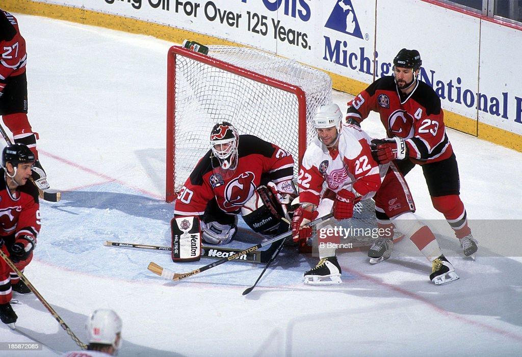 Goalie Martin Brodeur of the New Jersey Devils defends the net as his teammate Bruce Driver battles with Dino Ciccarelli of the Detroit Red Wings...
