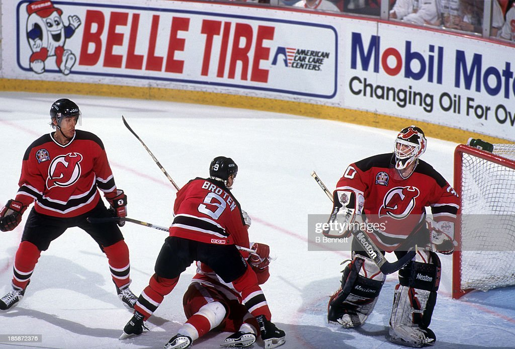 Goalie Martin Brodeur of the New Jersey Devils defends the net as his teammate Neal Broten knocks down an unidentified Detroit Red Wings player...