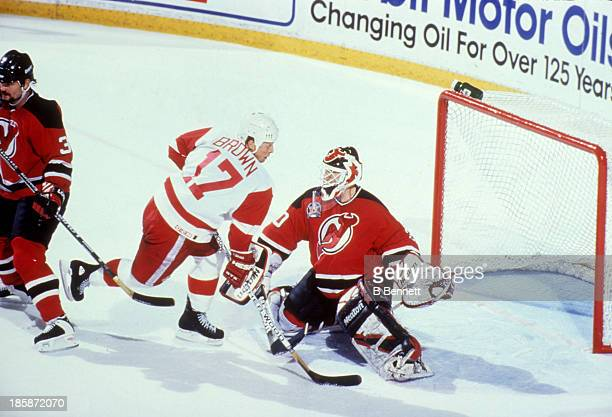 Goalie Martin Brodeur of the New Jersey Devils defends the net as Doug Brown of the Detroit Red Wings crashes the net during Game 1 of the 1995...