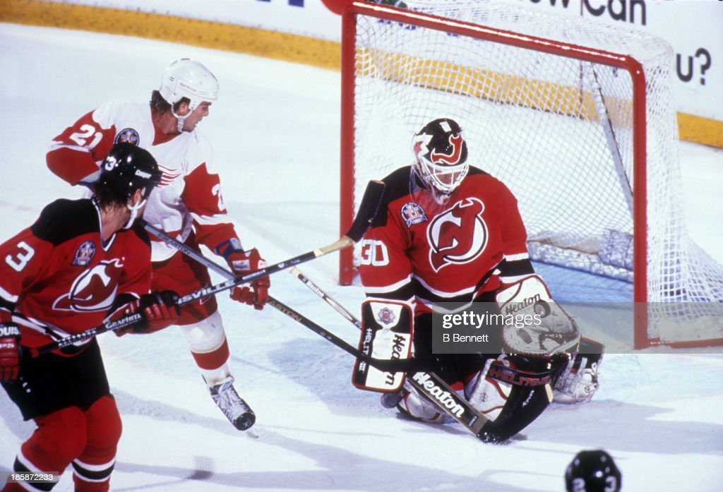 Goalie Martin Brodeur of the New Jersey Devils makes the save as Bob Errey of the Detroit Red Wings looks for the rebound as Ken Daneyko of the...