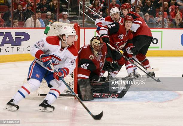 Goalie Mike Smith and Jakob Chychrun of the Arizona Coyotes watch as Sven Andrighetto of the Montreal Canadiens skates with the puck around the net...