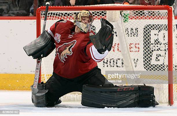 Goalie Mike Smith of the Arizona Coyotes makes a glove save on a shot by the Calgary Flames during the third period at Gila River Arena on December 8...