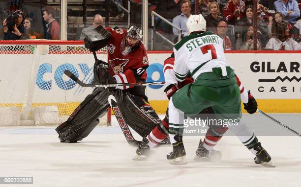 Goalie Mike Smith of the Arizona Coyotes skates out to clear the puck away from Chris Stewart of the Minnesota Wild during the second period at Gila...