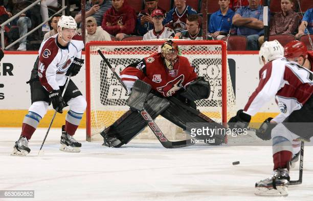 Goalie Mike Smith of the Arizona Coyotes watches the puck as Blake Comeau of the Colorado Avalanche positions himself in front of the net during the...