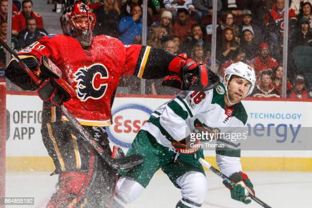 Goalie Mike Smith of the Calgary Flames pushes Cal OReilly of the Minnesota Wild in an NHL game against the Minnesota Wild at the Scotiabank...