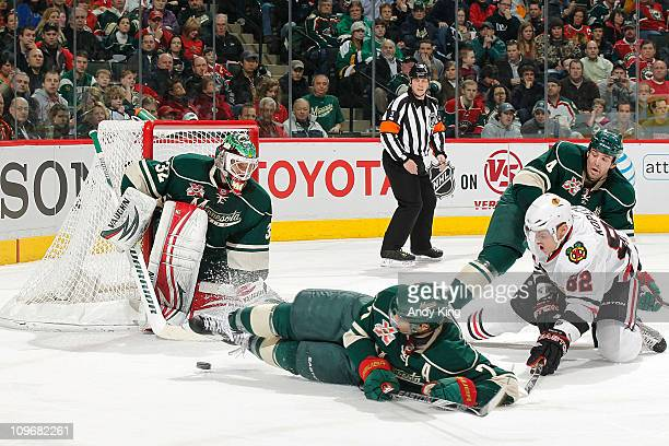 goalie Niklas Backstrom Matt Cullen and Clayton Stoner of the Minnesota Wild defend their goal against Tomas Kopecky and the Chicago Blackhawks...