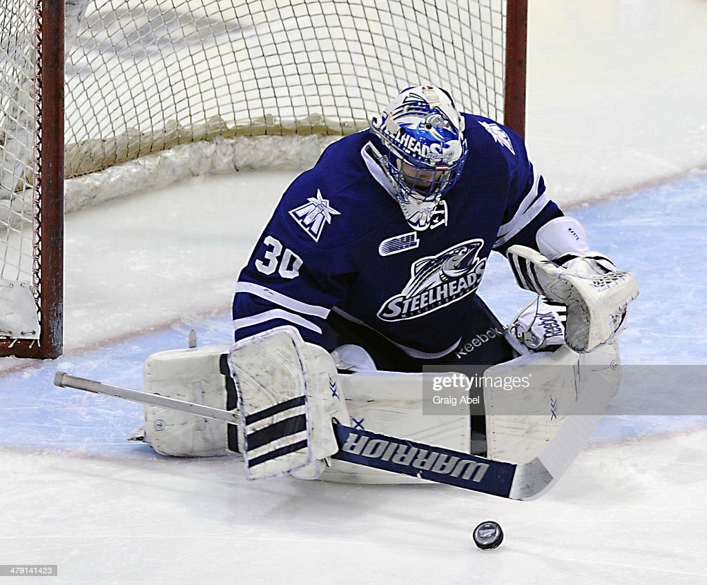 Goalie #30 of the Mississauga Steelheads stops a shot against the Kingston Frontenacs during game action on March 16, 2014 at the Hershey Centre in Mississauga, Ontario, Canada.