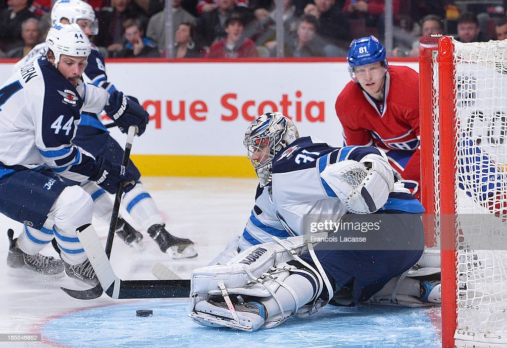 Goalie Ondrej Pavelec #31 of the Winnipeg Jets makes a pad save as teammate <a gi-track='captionPersonalityLinkClicked' href=/galleries/search?phrase=Zach+Bogosian&family=editorial&specificpeople=4195061 ng-click='$event.stopPropagation()'>Zach Bogosian</a> #44 prepares to clear the puck during the NHL game against the Montreal Canadiens on April 4, 2013 at the Bell Centre in Montreal, Quebec, Canada.