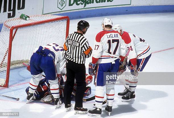 Goalie Patrick Roy of the Montreal Canadiens lies on the ice after being injured as his teammates Brian Bellows John LeClair and Lyle Odelein check...