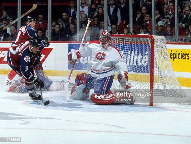 Goalie Patrick Roy of the Montreal Canadiens makes the save as Valeri Kamensky of the Colorado Avalanche goes for the rebound on November 25 1995 at...