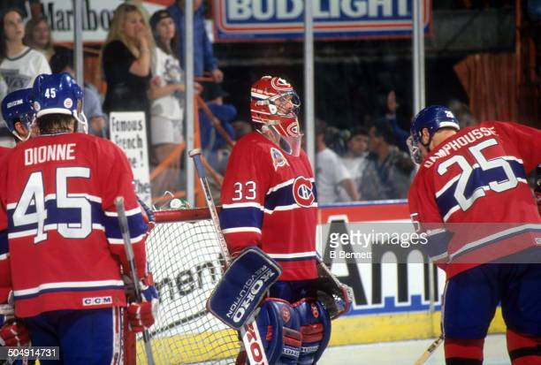 Goalie Patrick Roy of the Montreal Canadiens stands in front of the net as teammate Vincent Damphousse skates in front of him during Game 3 of the...