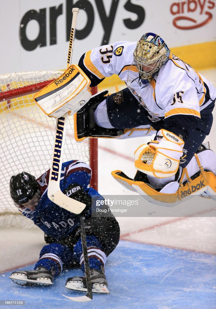 Goalie Pekka Rinne of the Nashville Predators leaps over a sliding Chuck Kobasew of the Colorado Avalanche to avoid a collision at the Pepsi Center...