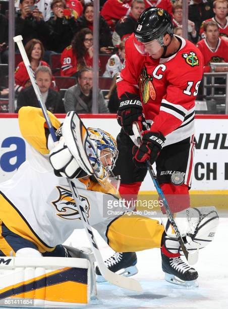 Goalie Pekka Rinne of the Nashville Predators reaches for the puck against Jonathan Toews of the Chicago Blackhawks in the second period at the...