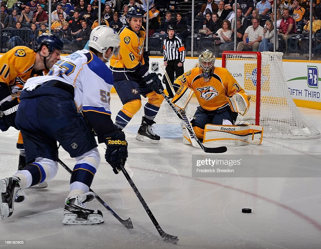 Goalie <a gi-track='captionPersonalityLinkClicked' href=/galleries/search?phrase=Pekka+Rinne&family=editorial&specificpeople=2118342 ng-click='$event.stopPropagation()'>Pekka Rinne</a> #35 of the Nashville Predators watches David Perron #57 of the St Louis Blues pursue the puck at the Bridgestone Arena on April 9, 2013 in Nashville, Tennessee.