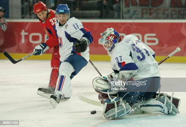 Goalie Peter Budaj of Slovakia makes a save as teammate Lubomir Visnovsky and Maxim Sushinsky of Russia look on during the third period of the men's...