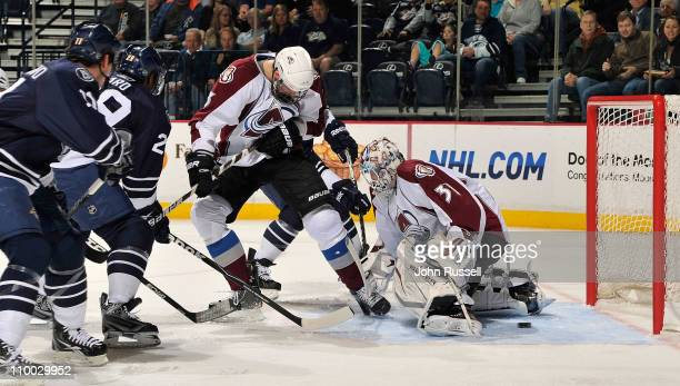 Goalie Peter Budaj of the Colorado Avalanche lets the puck in the net against Matt Halischuk of the Nashville Predators during an NHL game on March...