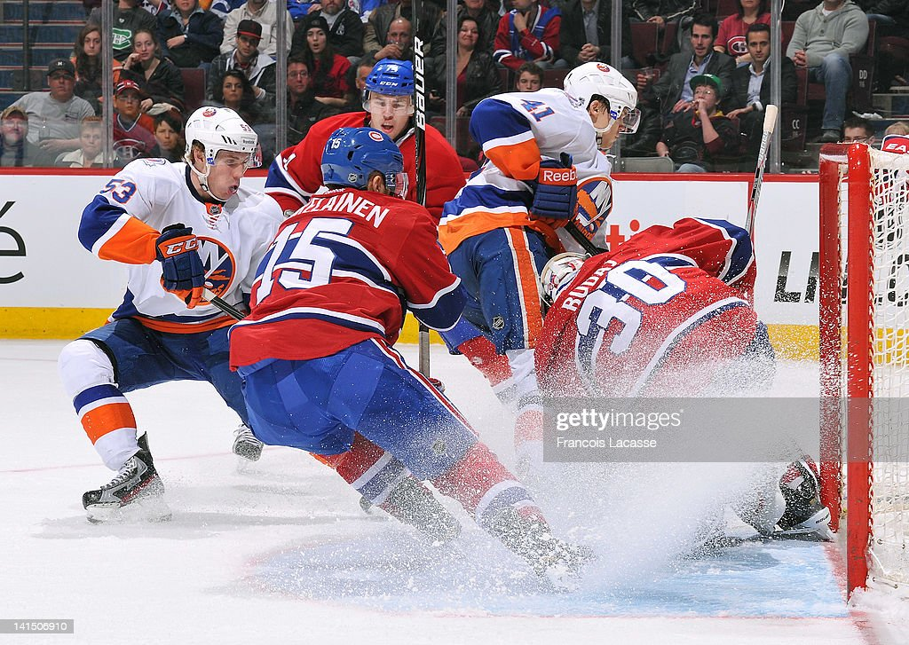 Goalie <a gi-track='captionPersonalityLinkClicked' href=/galleries/search?phrase=Peter+Budaj&family=editorial&specificpeople=228123 ng-click='$event.stopPropagation()'>Peter Budaj</a> #30 of the Montreal Canadiens gets help from teammate <a gi-track='captionPersonalityLinkClicked' href=/galleries/search?phrase=Petteri+Nokelainen&family=editorial&specificpeople=714450 ng-click='$event.stopPropagation()'>Petteri Nokelainen</a> #15 covering the puck as Casey Cizikas #53 and David Ullstrom #41 of the New York Islanders look for the rebound during the NHL game on March 17, 2012 at the Bell Centre in Montreal, Quebec, Canada.