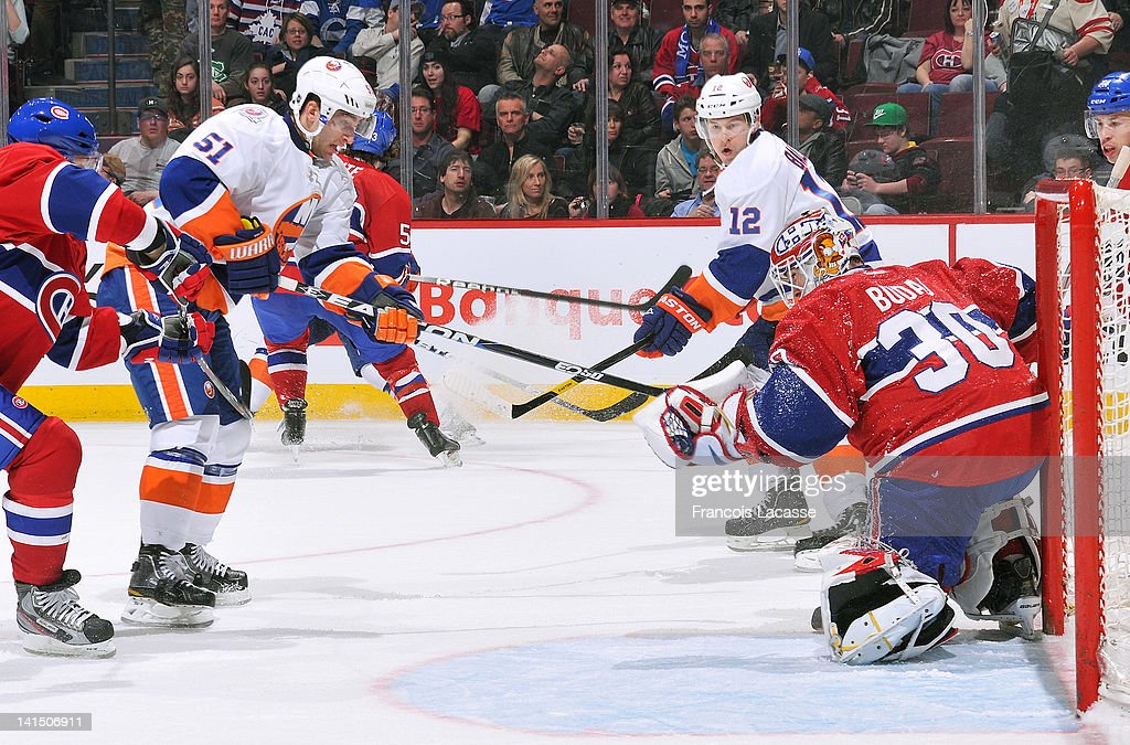 Goalie <a gi-track='captionPersonalityLinkClicked' href=/galleries/search?phrase=Peter+Budaj&family=editorial&specificpeople=228123 ng-click='$event.stopPropagation()'>Peter Budaj</a> #30 of the Montreal Canadiens gloves the puck as <a gi-track='captionPersonalityLinkClicked' href=/galleries/search?phrase=Frans+Nielsen&family=editorial&specificpeople=634894 ng-click='$event.stopPropagation()'>Frans Nielsen</a> #51 of the New York Islanders looks for the rebound during the NHL game on March 17, 2012 at the Bell Centre in Montreal, Quebec, Canada.